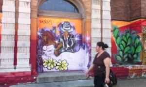 A Pilsen resident walks past colorful murals found on the walls of St. Pius V Church.
