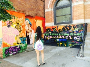 A Loyola student admires a stretch of wall art.